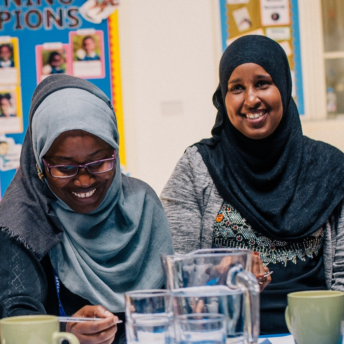 Two women sat at a table laughing at a community business event